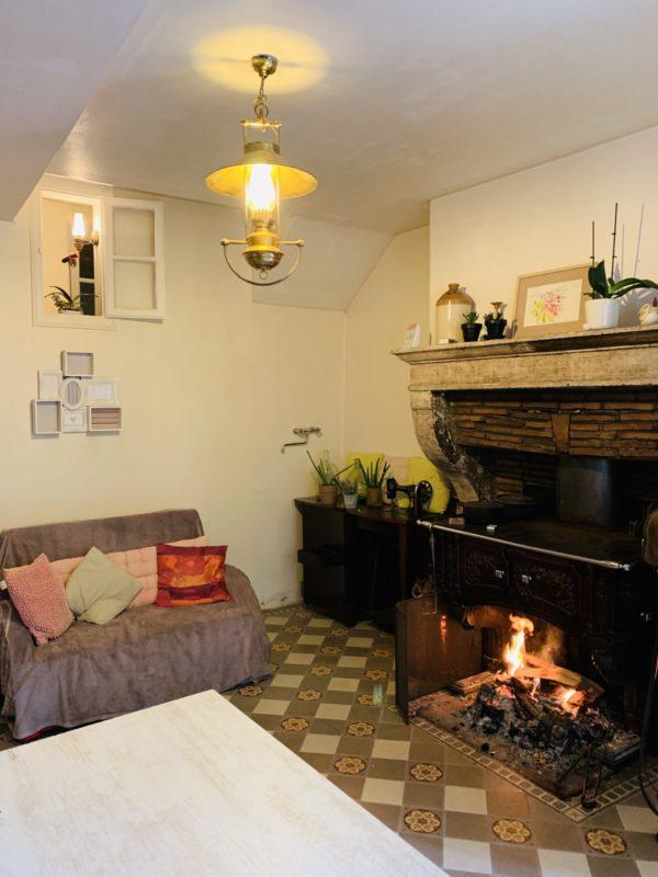 Piece commune des chambres d'hote de la pierre écrite. Un canapé devant une cheminé.